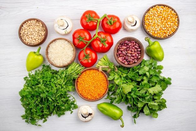 白い背景の上の緑のキノコのコショウの茎トウモロコシの穀粒豆の束とフレッシュトマトの上面図