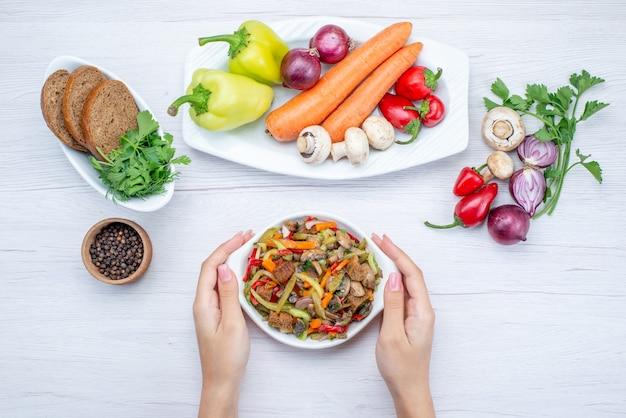 ライトデスクでパンローフと野菜と緑全体と一緒に肉でスライスした新鮮な野菜サラダの上面図、フードミールサラダビタミン料理