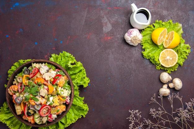 Вид сверху свежих овощей. салат с дольками лимона и зеленым салатом на черном