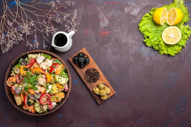 新鮮な野菜の上面図。黒にオリーブとレモンのスライスのサラダ