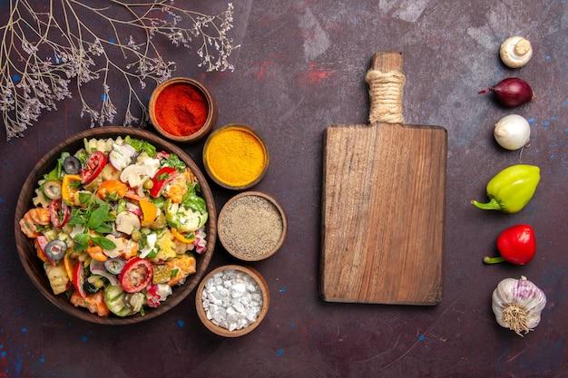 Вид сверху салата из свежих овощей с приправами на черном