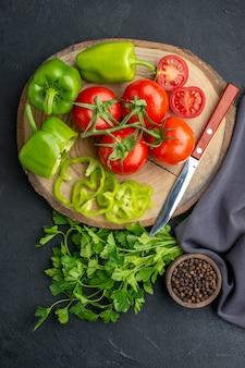 黒の苦しめられた表面のまな板緑の束のコショウの新鮮な野菜とナイフの上面図