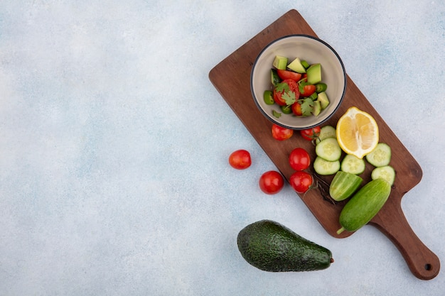 きゅうりのみじん切りの木製キッチンボード上のボウルにキュウリとトマトを含む新鮮な野菜のトップビュースライスチェリートマトレモネードアボカドホワイト 無料写真