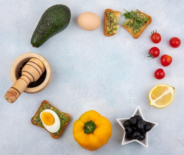 Вид сверху на свежие овощи, такие как авокадо, желтый болгарский перец, черные оливки, яйцо и поджаренный кусок хлеба с мякотью авокадо на белом с копией пространства