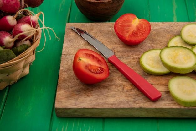 緑の木製の壁のバケツに大根とナイフで木製のキッチンボードに分離されたトマトやズッキーニの刻んだスライスなどの新鮮な野菜の上面図
