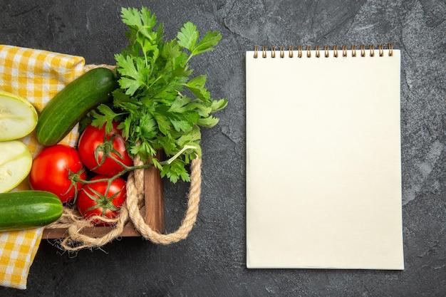 Вид сверху свежих овощей, красных помидоров, огурцов и кабачков с зеленью на серой поверхности