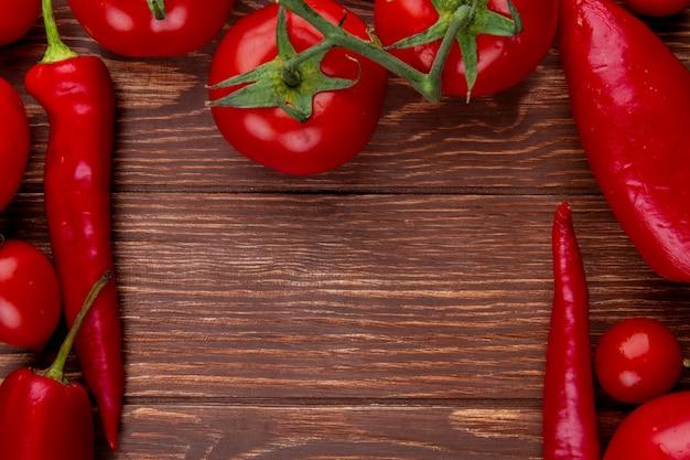 コピースペースを持つ素朴な木の上の赤唐辛子と新鮮な野菜の完熟トマトのトップビュー