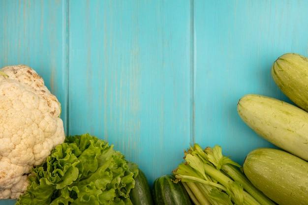 Вид сверху на свежие овощи, такие как цветная капуста, огурцы, салат, цуккини и сельдерей, изолированные на синей деревянной стене с копией пространства
