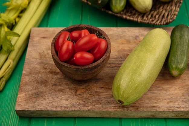 緑の木製の壁に分離されたセロリと木製のボウルに梅トマトと木製のキッチンボード上のキュウリズッキーニなどの新鮮な野菜の上面図