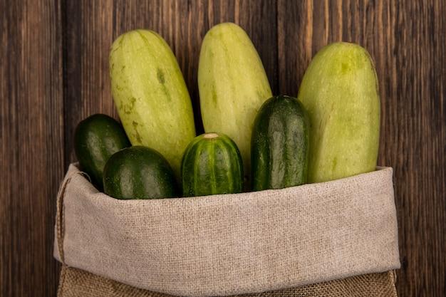 Вид сверху на свежие овощи, такие как огурцы и кабачки, на мешковине на деревянной стене