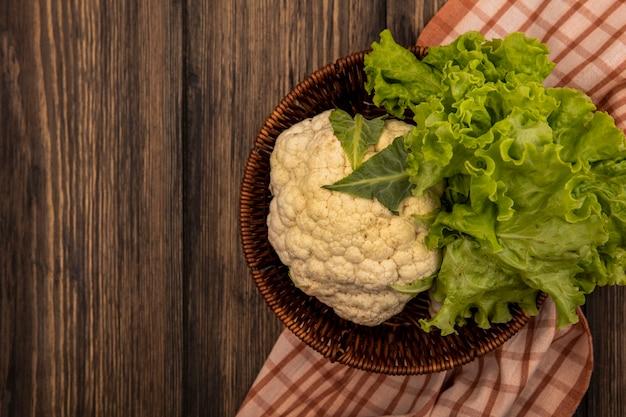 Вид сверху на свежие овощи, такие как салат и цветная капуста, на ведре на клетчатой ткани на деревянной стене с местом для копирования