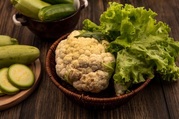 レタスやカリフラワーなどの新鮮な野菜をバケツに載せ、ズッキーニのみじん切りを木製のキッチンボードに、きゅうりを木製の表面のボウルに載せた上面図