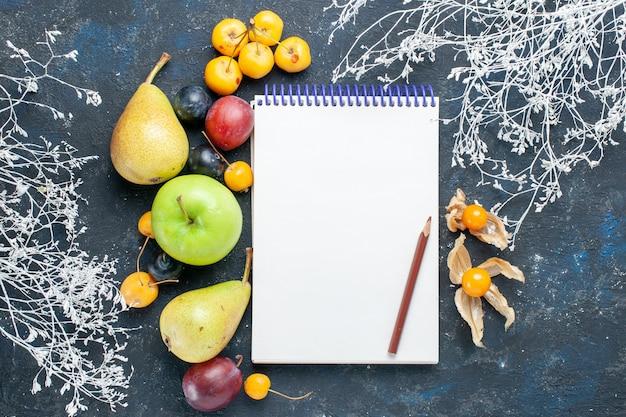 Вид сверху на свежие овощи, такие как груши, зеленое яблоко, желтые вишни, сливы и блокнот на темно-синем столе, фрукты, свежие ягоды