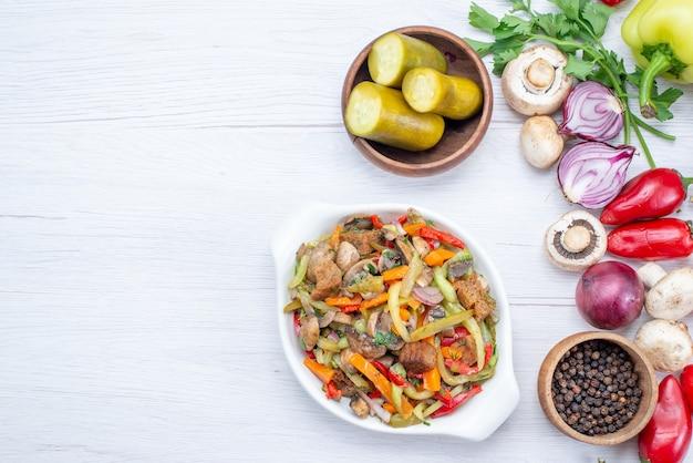 ライトデスクにスライスした肉料理と唐辛子にんじん玉ねぎ、野菜料理の食事のビタミンなどの新鮮な野菜の上面図