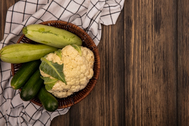 Вид сверху на свежие овощи, такие как цуккини, огурцы, цветная капуста на ведре на клетчатой ткани на деревянной стене с копией пространства