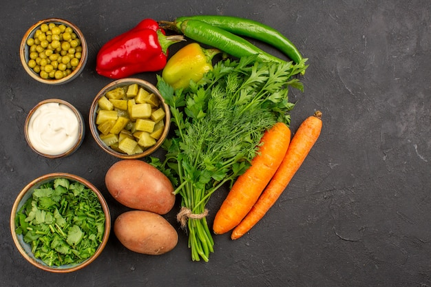 Вид сверху свежих овощей с зеленью на темной поверхности