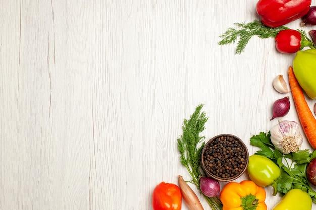 Вид сверху свежих овощей с зеленью на белом