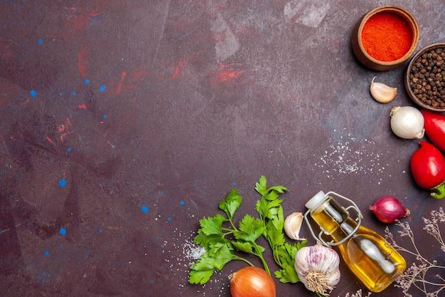 黒に調味料を入れた新鮮な野菜の上面図。テーブル