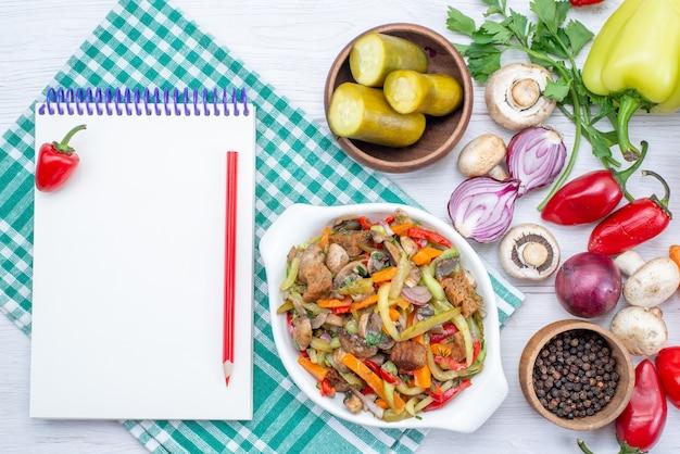 スライスした肉料理とライトデスクのメモ帳、野菜料理の食事の肉と新鮮な野菜の上面図