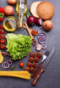 검은 색 표면에 향신료와 더 많은 음식과 신선한 야채의 상위 뷰