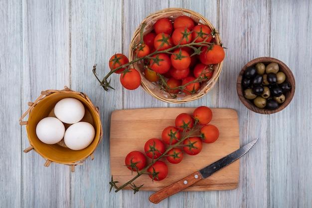 灰色の木製の背景の上の木製のボウルにつるのトマトとオリーブとバケツの上のナイフと木製のキッチンボード上の新鮮なつるのトマトの上面図