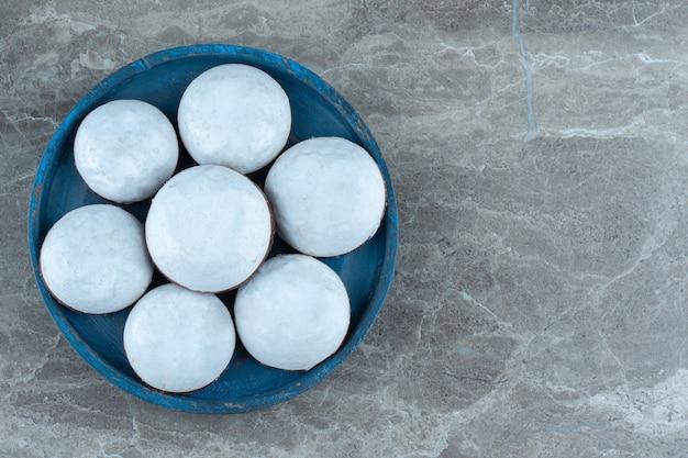 青い木製プレート上の新鮮なホワイトチョコレートクッキーの上面図。