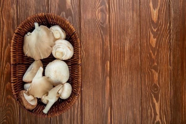 Взгляд сверху свежих белых грибов в плетеной корзине на деревенской древесине с космосом экземпляра