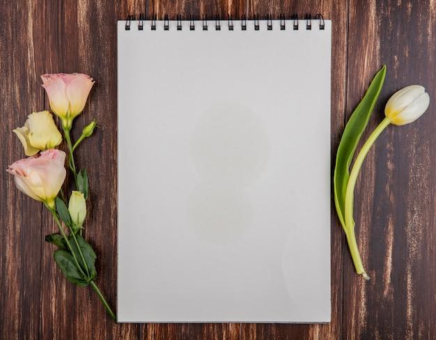 コピースペースと木製の背景にバラと新鮮な白いチューリップの上面図