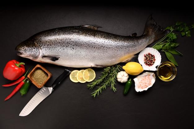Вид сверху свежих цельных рыбных морепродуктов лосося на черной каменной поверхности