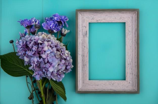 コピースペースと青い背景の上のデイジーやgardenziaなどの新鮮な素晴らしい花の上面図