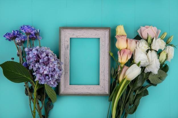 コピースペースと青い背景の上のバラのチューリップデイジーなどの新鮮な素晴らしい花の上面図