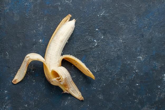 Вид сверху свежего желтого банана, сладкого и вкусного, очищенного на темно-синем столе, фруктовых ягод, сладких витаминов для здоровья