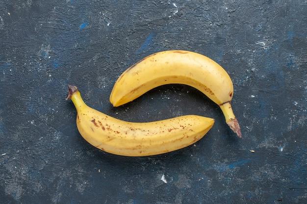 Вид сверху свежего желтого банана, сладкого и вкусного на темно-синем столе, фруктовых ягод, сладких витаминов для здоровья