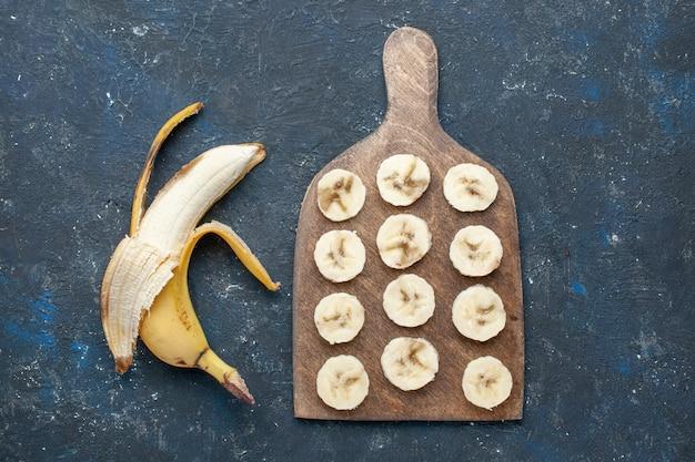 Вид сверху свежего желтого банана, сладкого и вкусного, очищенного и нарезанного на темно-синем столе, фруктовых ягод, сладких витаминов для здоровья