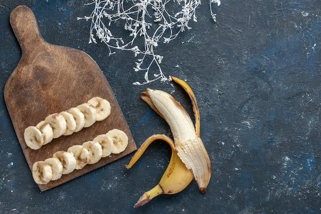 Вид сверху свежего желтого банана, сладкого и вкусного, нарезанного на темном столе, фруктовых ягод, сладких витаминов для здоровья