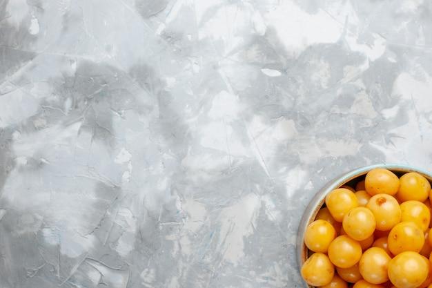 灰色のライトデスクのプレート内の新鮮な黄色のサクランボの上面図、フルーツ新鮮な夏の甘い