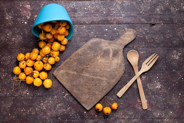 茶色の木製の机の上にまろやかでジューシーな新鮮な黄色のサクランボの上面図、熟した新鮮な果物