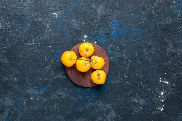 暗い机の上に分離された新鮮な黄色のサクランボの熟した甘い果実、フルーツベリーの新鮮なまろやかな上面図