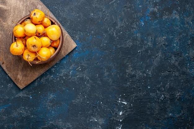 暗い机の上の新鮮な黄色のサクランボ熟した甘い果物、フルーツまろやかな新鮮な甘いチェリーの上面図