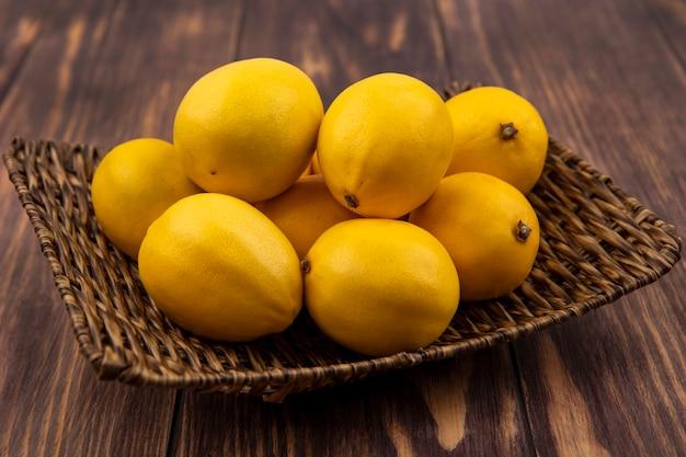 Вид сверху свежих желтых лимонов на плетеном подносе на деревянной стене