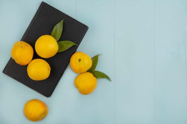 コピースペースと青色の背景に分離された新鮮な黄色の桃のトップビュー