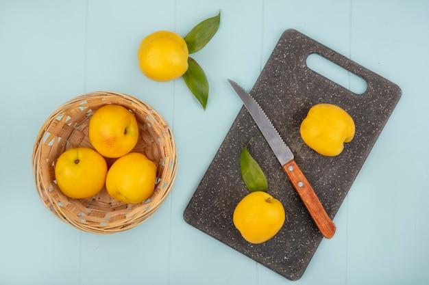 青色の背景にナイフでキッチンのまな板に桃とバケツに新鮮な黄色の桃のトップビュー