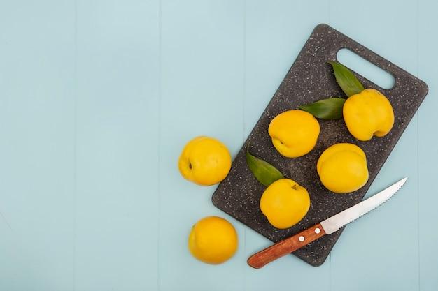 コピースペースと青色の背景にナイフでキッチンまな板の上の新鮮な黄色の桃のトップビュー