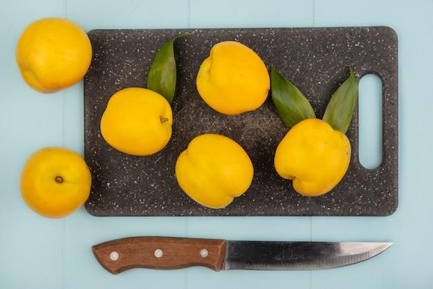 Вид сверху свежих желтых персиков на кухонной разделочной доске с ножом на синем фоне