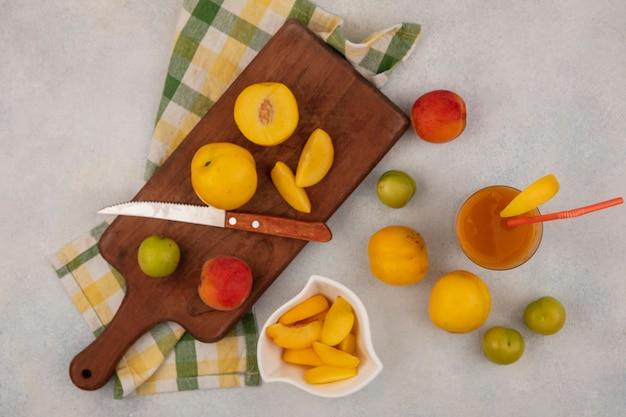 Вид сверху свежих желтых персиков на деревянной кухонной доске на клетчатой скатерти с ножом со свежим персиковым соком на стакане на белом фоне