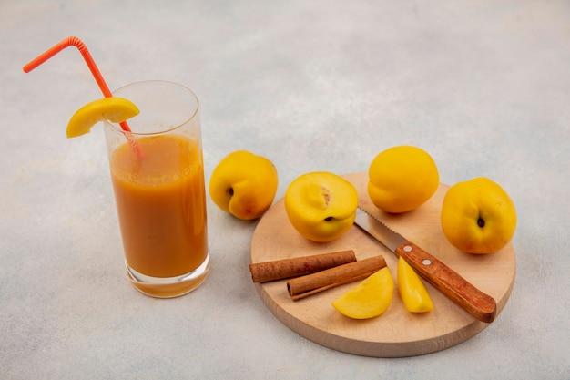 白い背景の上の新鮮な桃ジュースとシナモンスティックのナイフで木製キッチンボード上の新鮮な黄色の桃のトップビュー