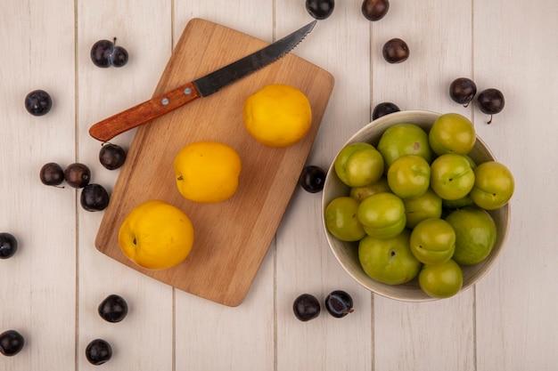 Вид сверху свежих желтых персиков на деревянной кухонной доске с ножом с зелеными алычами на миске с тёрном, изолированной на сером деревянном фоне