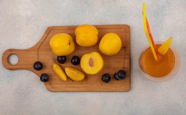 白い背景の上のガラスの新鮮な桃ジュースのスローと木製キッチンボード上の新鮮な黄色い桃のトップビュー
