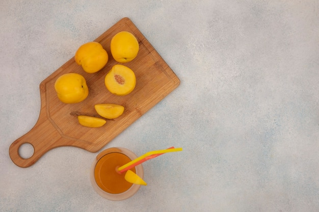 コピースペースと白い背景の上のガラスの新鮮な桃ジュースと新鮮な黄色い桃のトップビュー