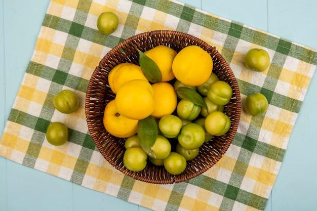 青色の背景にチェックされた布のバケツに緑のチェリープラムと新鮮な黄色の桃のトップビュー